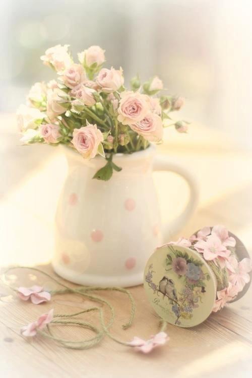 Petites roses dans un pichet ancien en porcelaine blanche avec des pois roses
