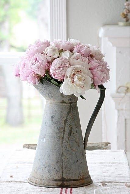 bouquet de pivoines roses et blanches dans un pichet en fer