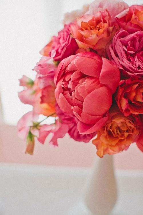 bouquet de pivoines rouges avec des roses oranges et quelques fleurs roses dans un vase blanc